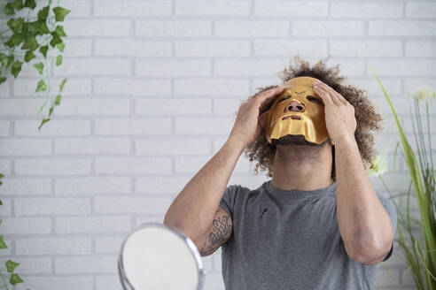 Young man applying facial mask while sitting against wall at home - SNF00342