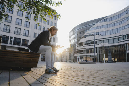 Businessman sitting on a bench in the city at sunset using tablet - JOSEF00815