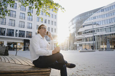 Businessman sitting on a bench in the city at sunset talking on the phone - JOSEF00818
