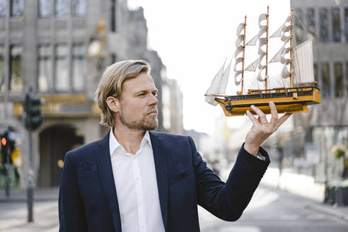 Businessman holding model ship in the city - JOSEF00839