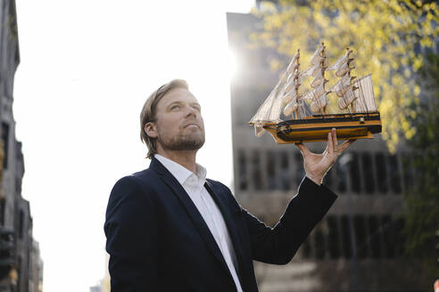Businessman holding model ship in the city - JOSEF00842