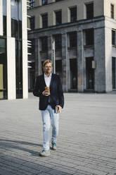 Businessman with takeaway coffee walking in the city - JOSEF00884