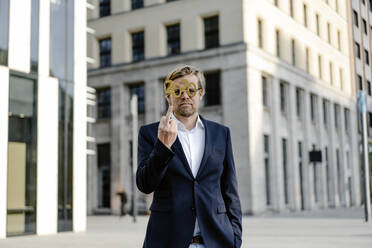 Businessman wearing 2020 comedy glasses in the city giving the finger - JOSEF00887