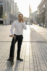 Businessman with kick scooter on the phone in the city - JOSEF00893