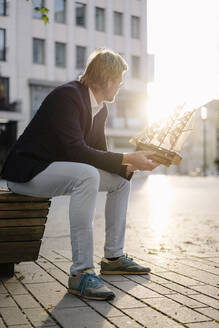 Businessman sitting on a bench in the city holding model ship - JOSEF00926
