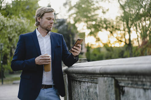Businessman with takeaway coffee using smartphone in city park - JOSEF00938