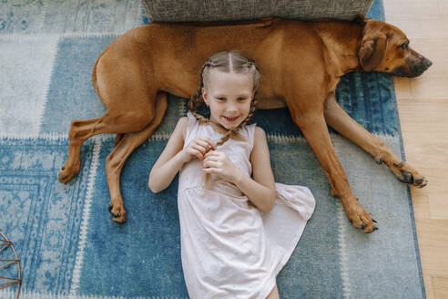 Cute girl with brown dog lying on carpet at home - OGF00450