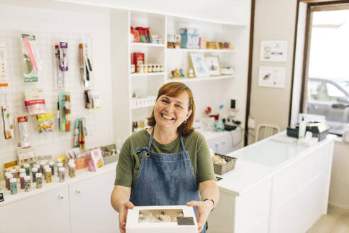 Smiling female baker delivering cupcake box while standing in store - GMLF00244