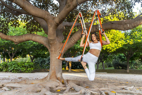 Woman practicing aerial yoga on hammock hanging over tree in park - DLTSF00775