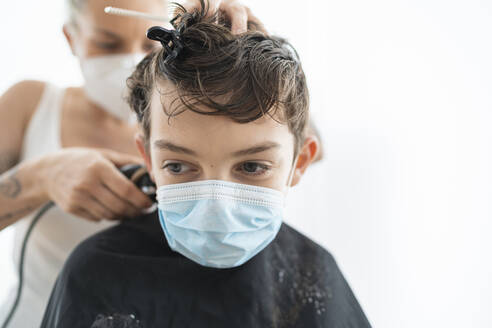 Close-up of hairdresser cutting boy's hair wearing mask at home during curfew - SNF00368