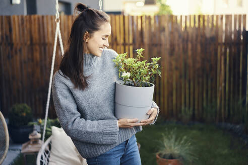 Happy young woman carrying potted plant while standing in garden - BSZF01569