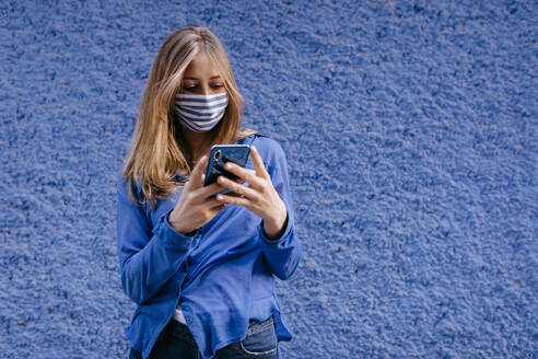Young woman wearing mask using smart phone while standing against wall in city - TCEF00764