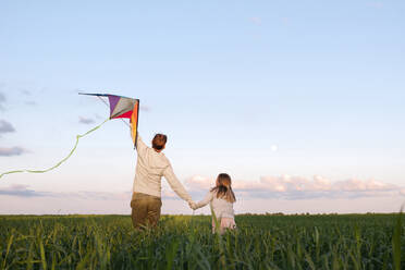 Man holding kite while walking with daughter amidst plants on green landscape - EYAF01161