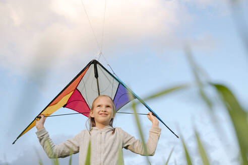Smiling girl holding kite while standing against sky - EYAF01164