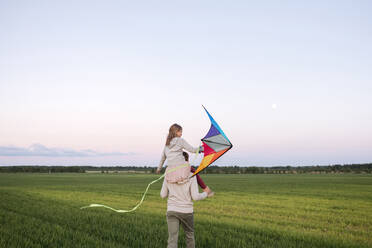 Father carrying daughter on shoulders while walking on grassy landscape at sunset - EYAF01167