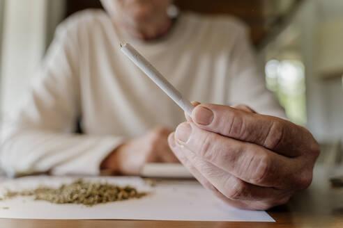 Close-up of senior man holding marijuana joint at home - AFVF06689