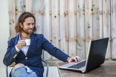 Handsome young businessman drinking espresso while using laptop at cafe - DLTSF00782