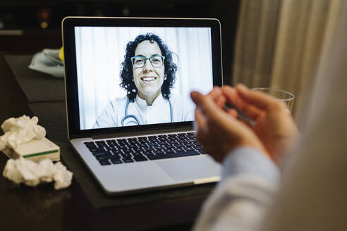 Retired senior ill woman discussing over video call with smiling doctor at home - XLGF00234