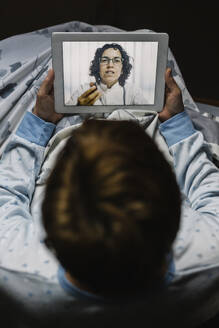 Retired ill woman discussing over video call through digital tablet with doctor in bedroom - XLGF00246