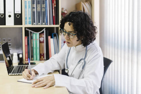 Female doctor writing by laptop while sitting at desk in office - XLGF00252