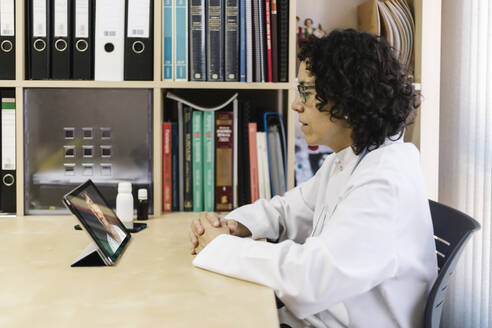 Doctor discussing illness with senior female patient through video call on digital tablet at medical clinic - XLGF00255