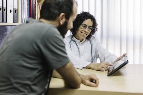 Smiling female doctor showing digital tablet to patient in clinic - XLGF00261