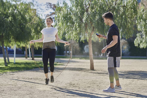 Woman during work out with coach skipping rope in park - JNDF00182