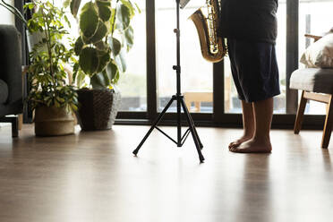 Crop view of boy exercising to play the saxophone at home - VABF03090