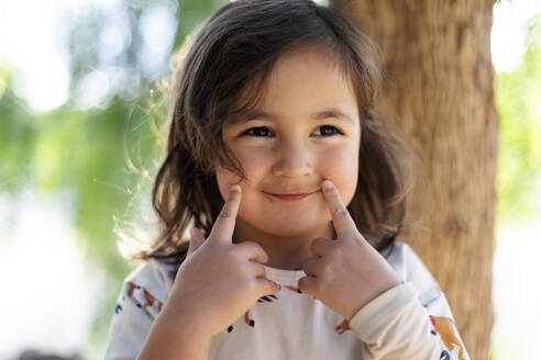 Portrait of smiling little girl with fingers on her face - VABF03096