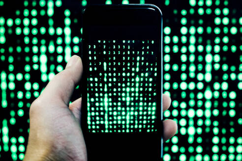 Cropped Hand Of Man Holding Mobile Phone With Binary Code - EYF07285