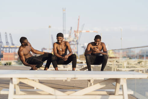 Happy shirtless young men sitting on picnic table against sky during sunny day - EGAF00242