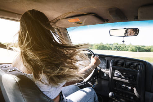 Woman with long blond tousled hair driving car on road trip - JCMF00899