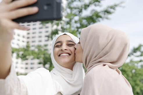 Muslim teenage girl holding folder while walking on sidewalk in city - JCZF00145