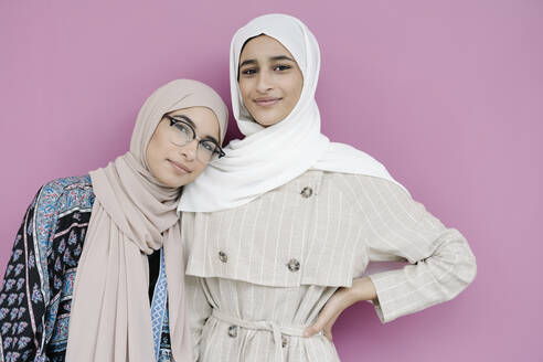 Muslim sisters standing together against purple background - JCZF00160