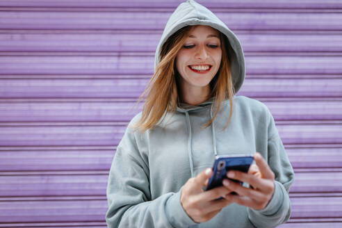 Portrait of young blonde woman with green hoodie and purple background - TCEF00788