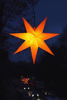 Star shaped Christmas decoration glowing outdoors at night - AXF00849