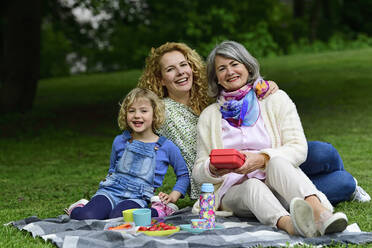 Happy boy enjoying picnic with mother and grandmother at public park - ECPF00964