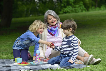 Happy grandmother looking at granddaughter drinking water during picnic at park - ECPF00967