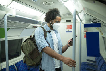 Man wearing protective mask standing in underground train looking at cell phone, London, UK - PMF01116