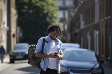 Smiling young man with backpack standing on residential street looking at cell phone, London, UK - PMF01119