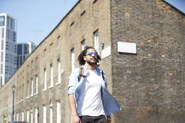 Portrait of young man with backpack and sunglasses walking on residential street, London, UK - PMF01122
