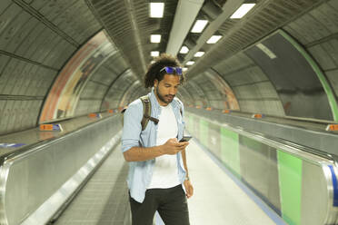 Portrait of young man looking at mobile phone, London, UK - PMF01125