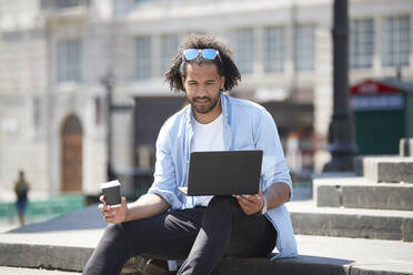 Portrait of young man with coffee to go sitting on stairs outdoors looking at laptop, London, UK - PMF01128