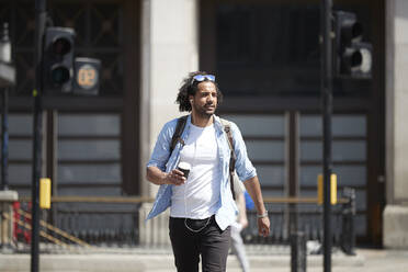 Portrait of young man with coffee to go crossing the street while listening music with earphones, London, UK - PMF01131