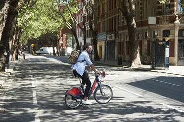 Young man using rental bike in the city, London, UK - PMF01137
