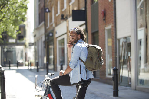 Portrait of smiling young man on the phone with rental bike and backpack in the city, London, UK - PMF01143