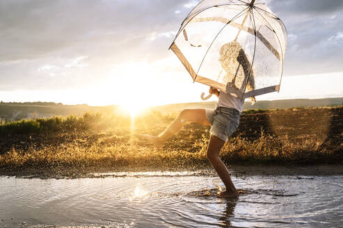 Girl with transparent umbrella splashing water on puddle against sky during sunset - JCMF00933