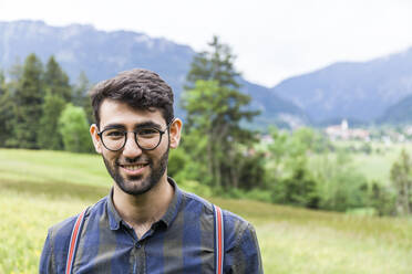 Portrait of smiling young man wearing glasses, Reichenwies, Oberammergau, Gerrmany - TCF06290