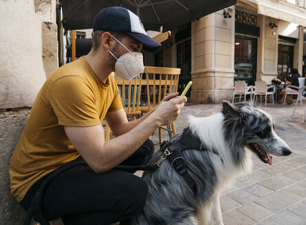 Man wearing protective mask waiting with his dog in the city using smartphone - AGGF00088