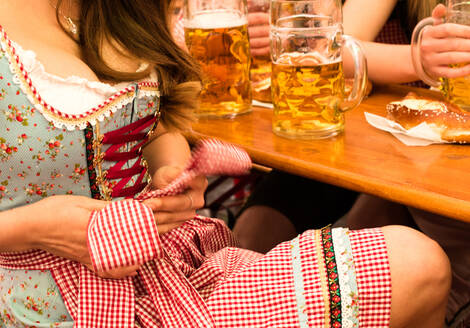 Midsection Of Woman Adjusting Dirndl By Table At Restaurant - EYF07787